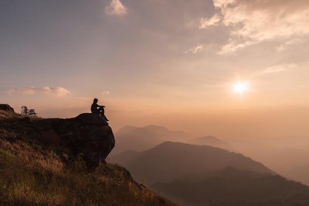 Junger reisender, der schöne landschaft auf berg, abenteuerreiselebensstilkonzept sich entspannt und schaut