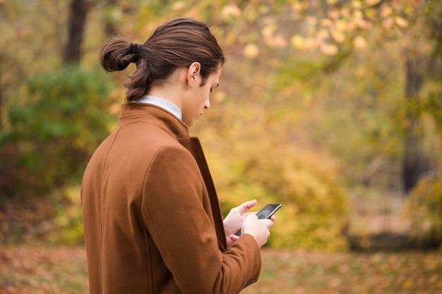 Junger reisender, der sein telefon im park überprüft