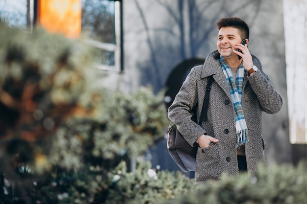 Junger reisender des gutaussehenden mannes, der draußen telefon verwendet