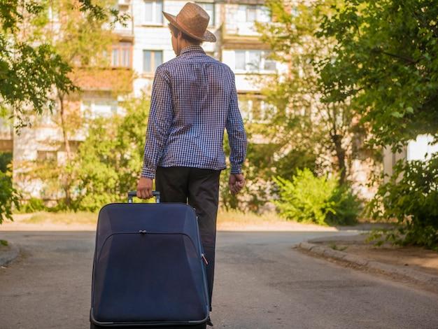 Junger reisender jugendlicher, der großen koffer in der sommerstadtstraße zieht