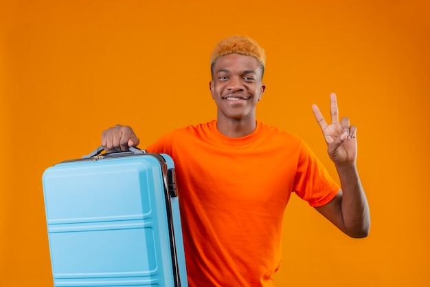 Junger reisender junge, der das orange t-shirt hält, das den lächelnden koffer hält und nummer zwei oder siegeszeichen zeigt, das über orange wand steht