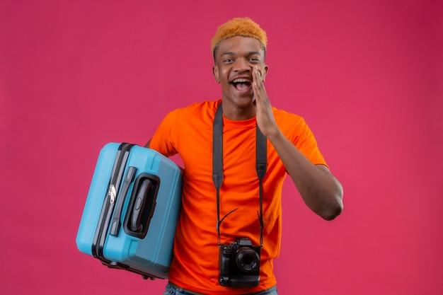 Junger reisender junge, der orange t-shirt hält, das koffer positiv und glücklich lächelndes sprichwort mit hand nahe mund hält über rosa wand hält