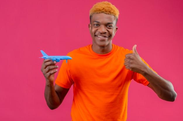 Junger reisender junge, der orange t-shirt hält, das lächelndes spielzeugflugzeug hält, das daumen oben zeigt über rosa wand