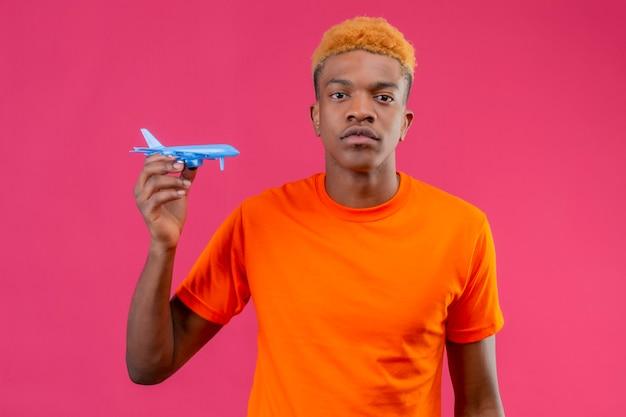 Junger reisender junge, der orange t-shirt hält spielzeugflugzeug mit ernstem selbstbewusstem ausdruck steht über rosa wand