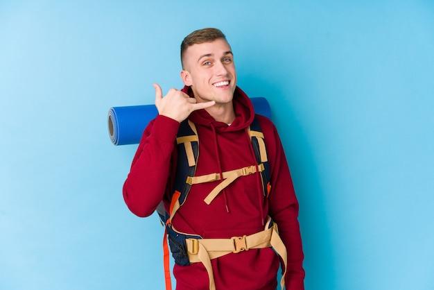 Junger reisender kaukasischer mann, der eine handy-anrufgeste mit den fingern zeigt.