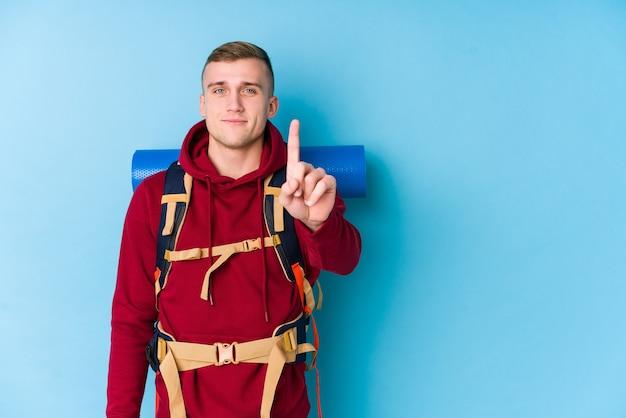 Junger reisender kaukasischer mann, der nummer eins mit finger zeigt.
