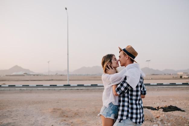 Junger reisender kerl im stilvollen hut und frau im niedlichen küssen des trendigen outfits küsst nahe der straße am wochenende. entzückende junge frau, die ihren hübschen freund sanft umarmt und auf natur lächelt