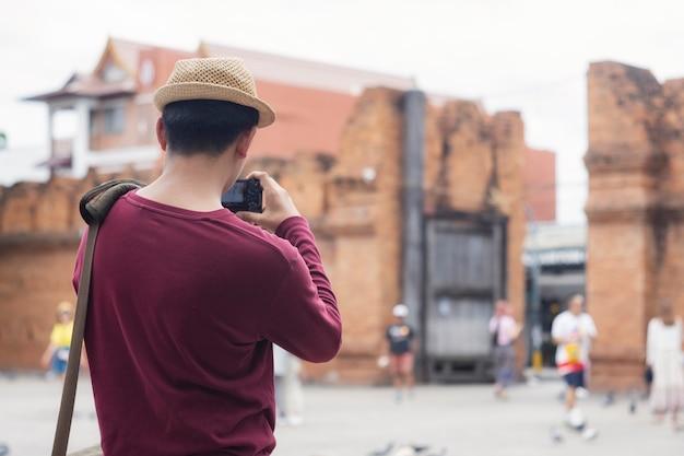 Junger reisender machen ein foto mit digitalkamera.