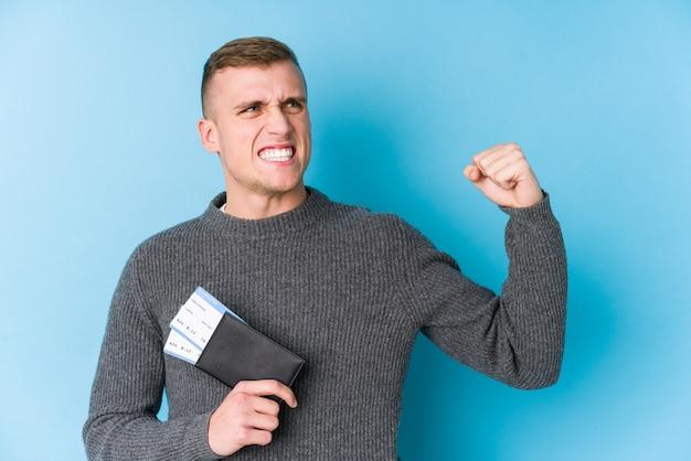 Junger reisender mann, der eine bordkarte hält, die faust nach einem sieg hebt