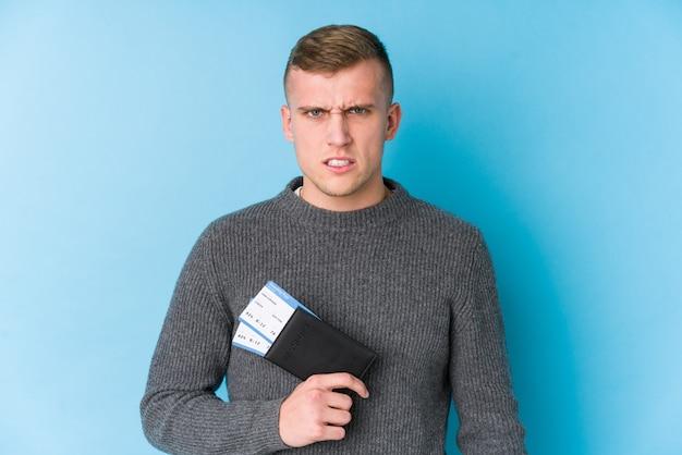 Junger reisender mann, der eine bordkarte hält, die sehr wütend und aggressiv schreit.