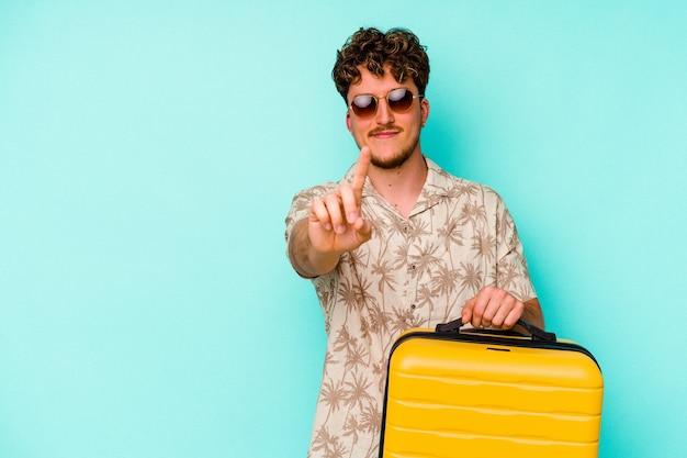 Junger reisender mann, der einen gelben koffer an der blauen wand hält, die nummer eins mit finger zeigt.