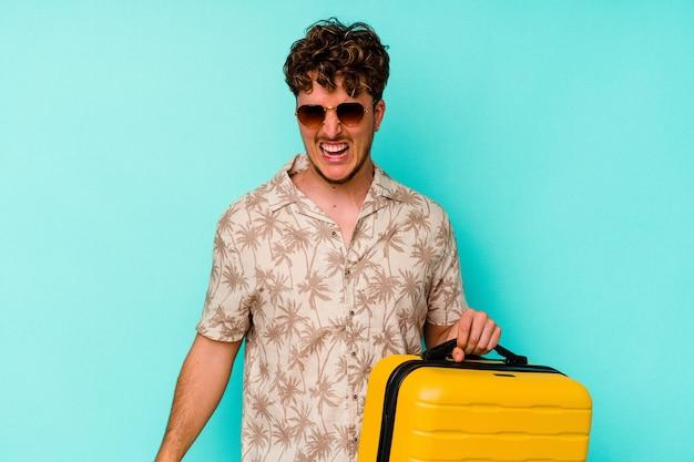 Junger reisender mann, der einen gelben koffer an der blauen wand hält, die sehr wütend und aggressiv schreit.