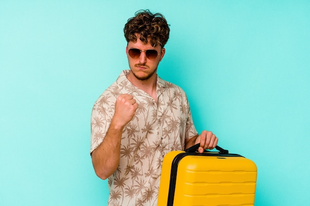 Junger reisender mann, der einen gelben koffer auf blauem hintergrund hält, der faust zur kamera, aggressiven gesichtsausdruck zeigt.
