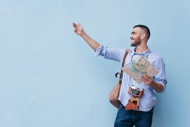 Junger reisender mann, der etwas mit der haltekarte zeigt, die gegen blauen hintergrund steht