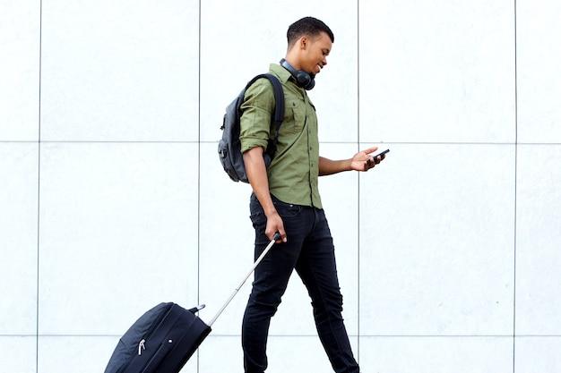 Junger reisender mann, der mit koffer und mobiltelefon geht