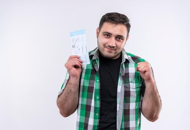 Junger reisender mann im karierten hemd, das flugkarten hält geballte faust glücklich und positiv lächelnd steht über weißer wand