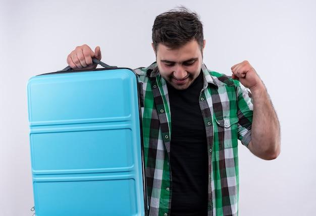 Junger reisender mann im karierten hemd, das koffer glücklich und aufgeregt geballte faust hält, gewinnerkonzept, das über weißer wand steht