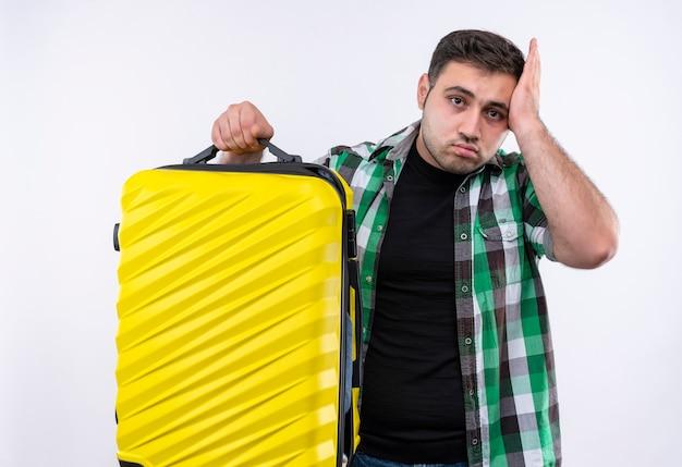 Junger reisender mann im karierten hemd, das koffer hält, der verwirrenden berührenden kopf für fehler steht, der über weißer wand steht
