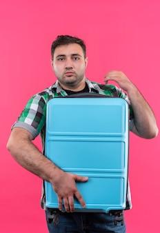 Junger reisender mann im karierten hemd, das koffer hält, der verwirrt und sehr besorgt über rosa wand steht
