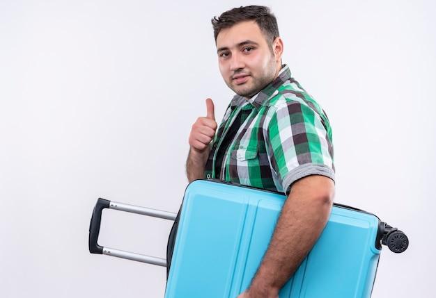Junger reisender mann im karierten hemd, das koffer hält, der zuversichtlich zeigt daumen zeigt, die über weißer wand stehen