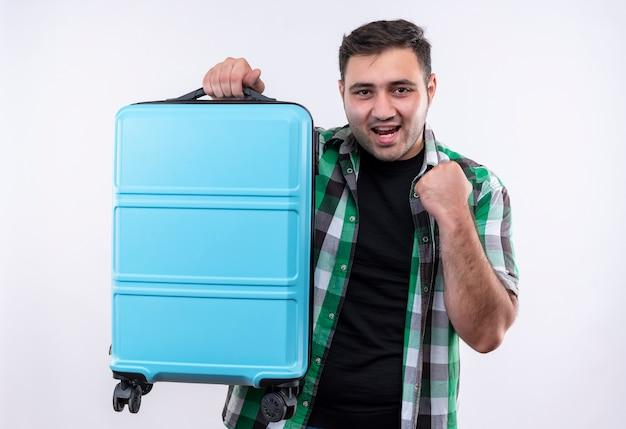 Junger reisender mann im karierten hemd, das koffer hält geballte faust glücklich und verlassen steht über weißer wand