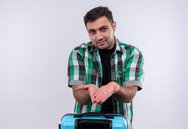 Junger reisender mann im karierten hemd, das koffer hält hände zeigt, die um geld bitten, das über weißer wand steht