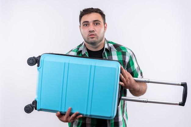 Junger reisender mann im karierten hemd, das koffer mit traurigem ausdruck auf gesicht steht, das über weißer wand steht