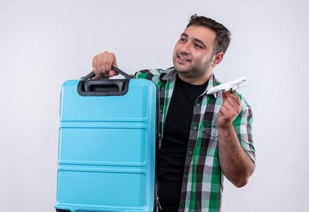 Junger reisender mann im karierten hemd, das koffer und spielzeugflugzeug hält, das seitwärts mit lächeln auf gesicht steht, das über weißer wand steht
