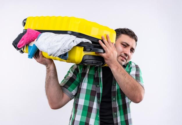 Junger reisender mann im karierten hemd, das koffer voll von kleidern hält, die enttäuscht stehen über weißer wand stehen