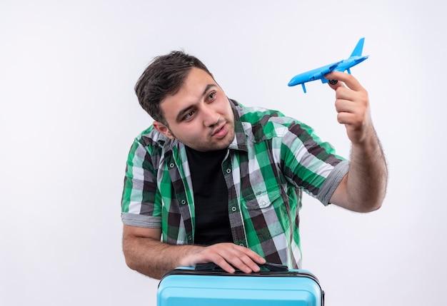 Junger reisender mann im karierten hemd stehend mit koffer, der spielzeugflugzeug hält, das mit glücklichem gesicht über weißer wand lächelt