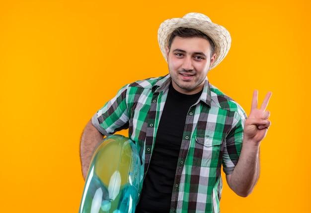 Junger reisender mann im karierten hemd und im sommerhut, der aufblasbaren ring hält, der das siegeszeichen zeigt, das über orange wand lächelnd steht