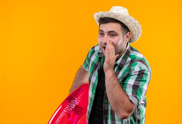 Junger reisender mann im karierten hemd und im sommerhut, der aufblasbaren ring hält, der ein geheimnis mit hand nahe mund erzählt über orange wand steht