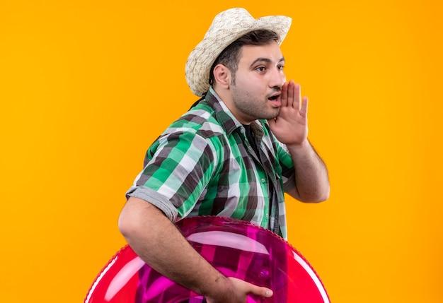 Junger reisender mann im karierten hemd und im sommerhut, der aufblasbaren ring hält, der jemanden mit der hand nahe mund über orange wand schreit oder ruft