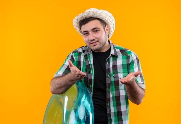 Junger reisender mann im karierten hemd und im sommerhut, der aufblasbaren ring mit erhobenen armen hält, als frage stellen, die über orange wand steht