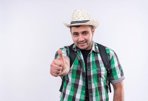 Junger reisender mann im karierten hemd und im sommerhut mit dem rucksack, der mit glücklichem gesicht lächelt, das daumen oben zeigt über weißer wand