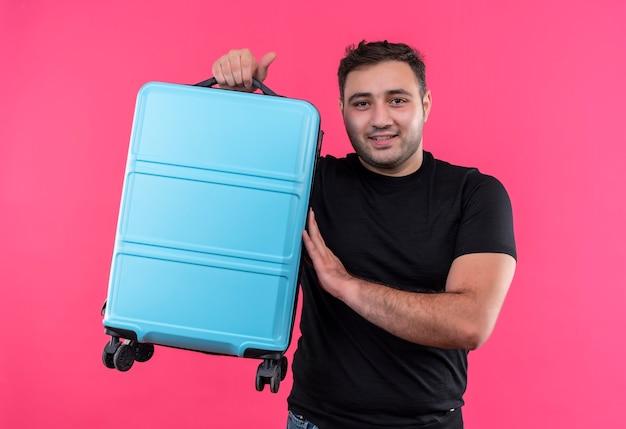 Junger reisender mann im schwarzen t-shirt, das koffer glücklich und positiv mit lächeln auf gesicht hält, das über rosa wand steht