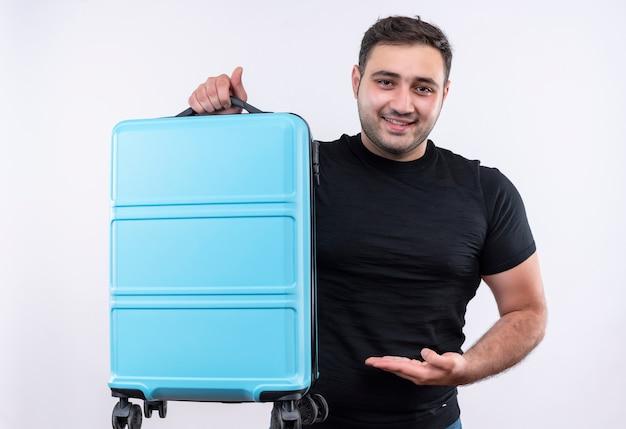 Junger reisender mann im schwarzen t-shirt, das koffer hält, der es mit dem arm präsentiert, der zuversichtlich weiß über der weißen wand steht