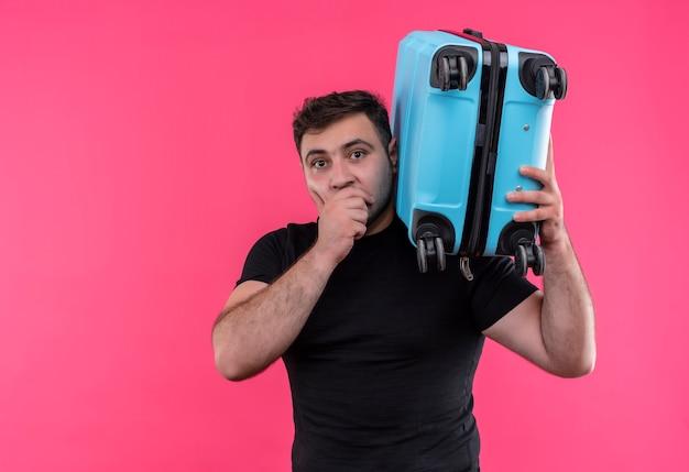 Junger reisender mann im schwarzen t-shirt, das koffer hält, der schockiert über rosa wand steht
