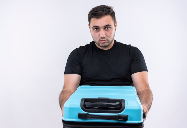 Junger reisender mann im schwarzen t-shirt, das koffer mit ernstem gesicht hält über weißer wand hält