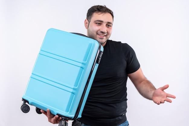 Junger reisender mann im schwarzen t-shirt, der koffer hält, der beiseite lächelt und fröhlich mit arm zur seite stehend über weiße wand spreizt