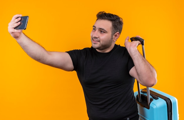 Junger reisender mann im schwarzen t-shirt, der koffer hält, der selfie nimmt, sein smartphone verwendet, das zur kamera lächelt, die über orange wand steht