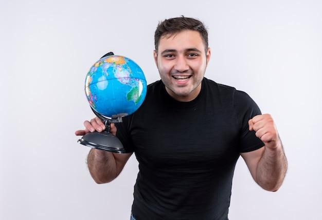 Junger reisender mann im schwarzen t-shirt hält globus, der faust glücklich und positiv lächelt, breit stehend über weißer wand
