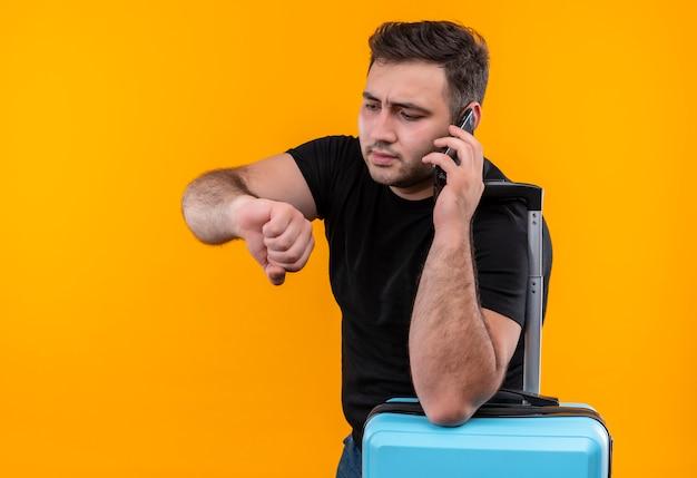 Junger reisender mann im schwarzen t-shirt mit koffer, der seine hand betrachtet, die sich an zeit erinnert, die auf handy mit ernstem gesicht über orange wand steht