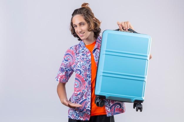 Junger reisender mann mit blauem koffer, der zuversichtlich lächelnd mit glücklichem gesicht bereit steht, stehend zu reisen
