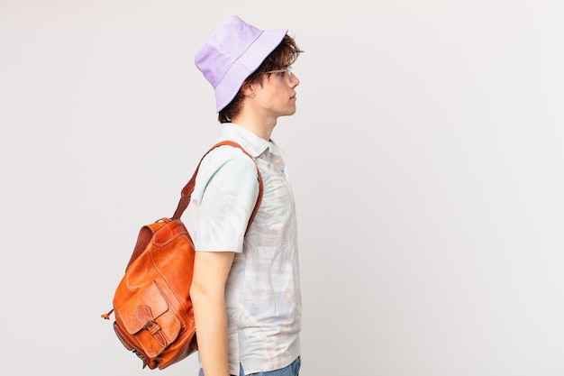 Junger reisender oder touristenmann auf profilansicht denken, sich vorstellen oder tagträumen
