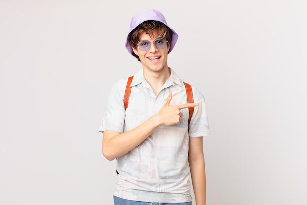 Junger reisender oder touristenmann, der aufgeregt und überrascht zur seite zeigt