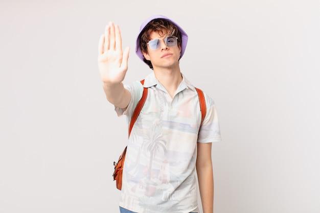 Junger reisender oder touristenmann, der ernst schaut und offene handfläche zeigt, die stoppgeste macht