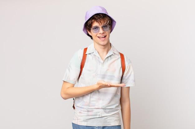 Junger reisender oder touristenmann, der fröhlich lächelt, sich glücklich fühlt und ein konzept zeigt