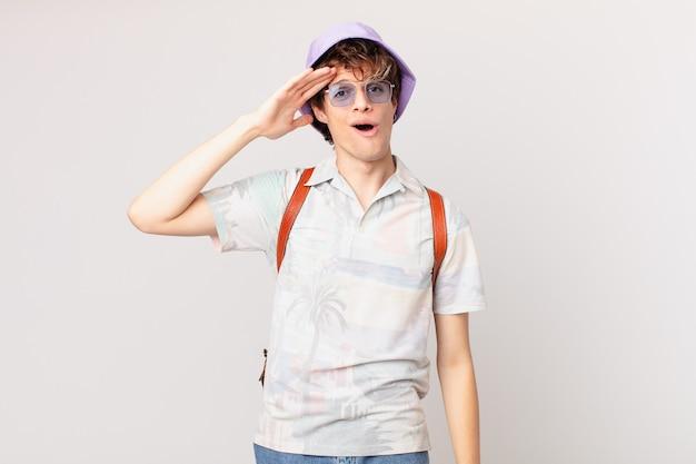 Junger reisender oder touristenmann, der glücklich, erstaunt und überrascht aussieht