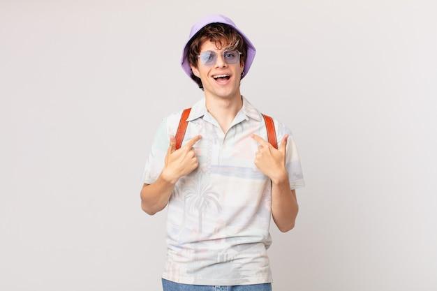 Junger reisender oder touristenmann, der glücklich fühlt und mit aufgeregtem auf sich selbst zeigt